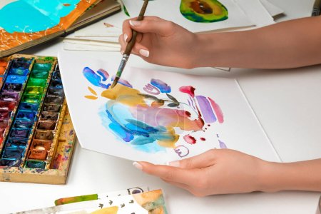 Photo for Selective focus of female hands drawing on paper with watercolor paints and paintbrush - Royalty Free Image