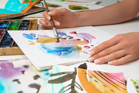 Photo pour Mise au point sélective des mains féminines dans l'album avec les peintures aquarelles et pinceau de dessin - image libre de droit