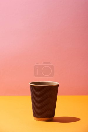 Photo pour Tasse de café en papier sur fond jaune de surface et rose - image libre de droit