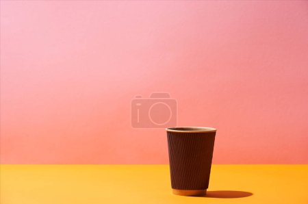 Photo for Paper coffee cup on yellow surface and pink background - Royalty Free Image
