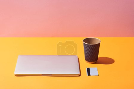 Foto de Paper coffee cup near laptop and credit card on yellow surface and pink background - Imagen libre de derechos