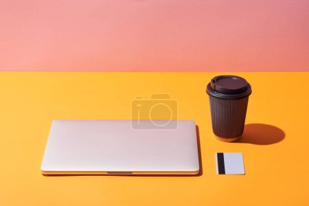 paper coffee cup near laptop and credit card on yellow surface and pink background