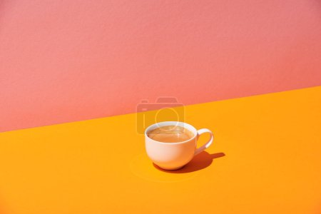 coffee cup on yellow surface and pink background