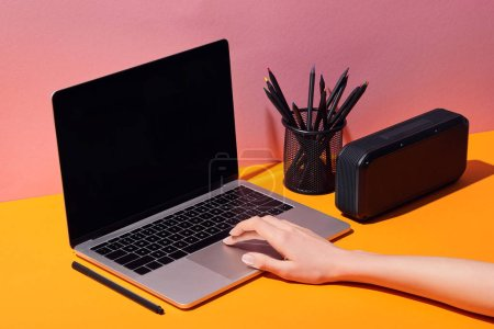Photo for Cropped view of woman using laptop with blank screen near pencil holder and speaker - Royalty Free Image