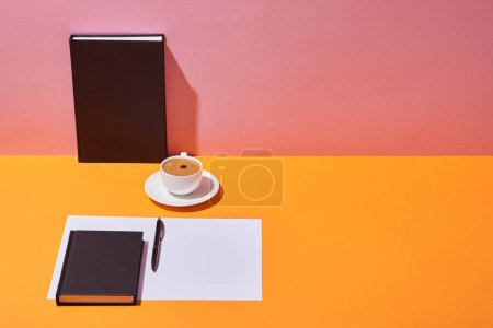 Photo for Notebooks, coffee cup, saucer, paper sheet and pen on yellow desk and pink background - Royalty Free Image