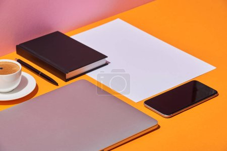 notebook, laptop, smartphone, coffee cup, saucer and paper sheet on yellow desk and pink background