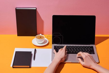 Photo for Cropped view of woman using laptop with blank screen near coffee cup, saucer, pen, paper sheet and notebooks on yellow desk and pink background - Royalty Free Image