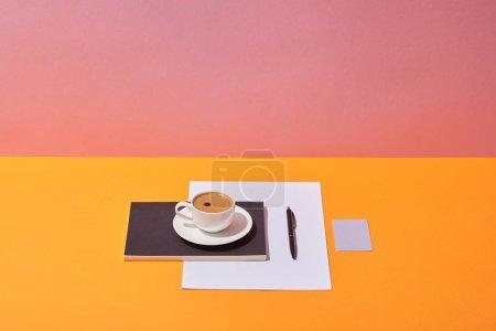 Photo pour Tasse à café, soucoupe, plume, feuille de papier et bloc-notes sur le bureau jaune et fond rose - image libre de droit