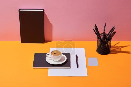 coffee cup, saucer, pen, paper sheet, pencil holder and notebook on yellow desk and pink background