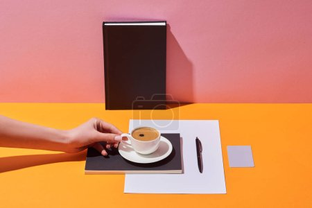 Photo for Cropped view of woman holding coffee cup near saucer, pen, paper sheet and notebooks on yellow desk and pink background - Royalty Free Image