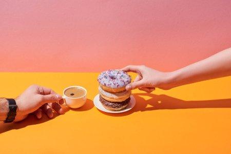 vista recortada de la mujer y el hombre tomando sabrosas rosquillas en platillo y taza de café en escritorio amarillo y fondo rosa