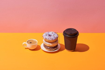Photo for Tasty donuts on saucer and coffee cups on yellow desk and pink background - Royalty Free Image