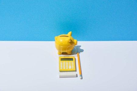Foto de Calculator, piggy bank, eraser and pencil on white desk and blue background - Imagen libre de derechos