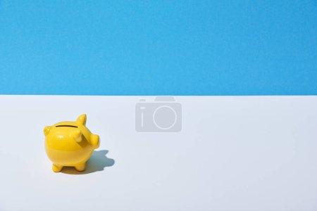 Foto de Amarillo hucha en escritorio blanco y fondo azul - Imagen libre de derechos