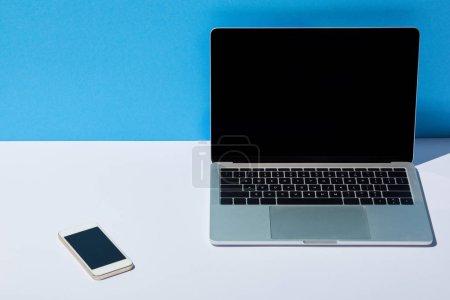 Photo pour Ordinateur portable avec écran blanc et smartphone sur bureau blanc et fond bleu - image libre de droit