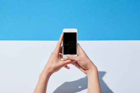 Photo for Cropped view of woman using smartphone with blank screen on white desk and blue background - Royalty Free Image