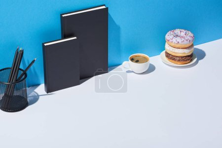 Photo for Tasty donuts, coffee cup, pencil holder and notebooks on white desk and blue background - Royalty Free Image