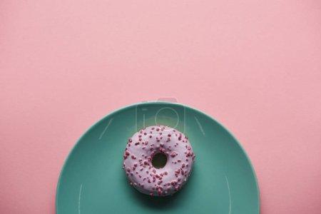 Foto de Vista superior de buñuelo esmaltado en azul placa aislada en rosa - Imagen libre de derechos