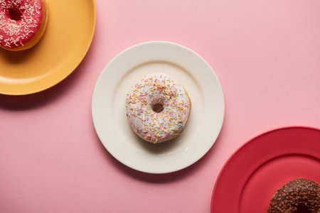 Photo for Top view of sweet delicious donuts on plates on pink background - Royalty Free Image