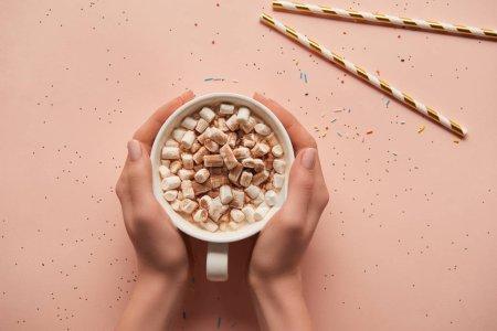 Photo pour Vue recadrée de femme tenant la tasse de chocolat chaud sur fond rose - image libre de droit