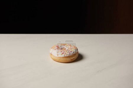 Photo for Sweet donut on white table isolated on black - Royalty Free Image