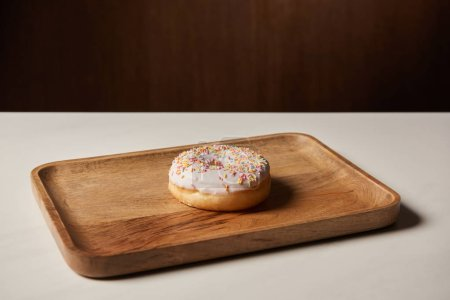 Photo for Tasty donut with sprinkles on wooden cutting board - Royalty Free Image