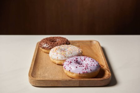 Photo for Sweet glazed doughnuts with sprinkles on wooden cutting board - Royalty Free Image