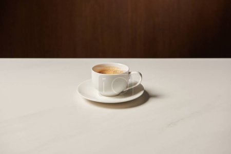 Photo for Cup of hot aromatic coffee on white table - Royalty Free Image