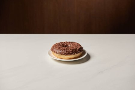 Photo for Glazed chocotale doughnut with sprinkles on white table - Royalty Free Image