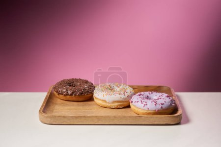 Photo for Tasty donuts with icing on wooden cutting board on pink background - Royalty Free Image