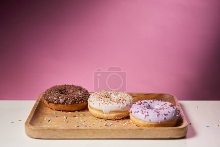 Photo for Tasty glazed donuts sprinkles on wooden cutting board on pink background - Royalty Free Image