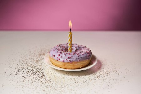 Photo for Burning candle in middle of glazed doughnut with sparkles on white table on pink background - Royalty Free Image