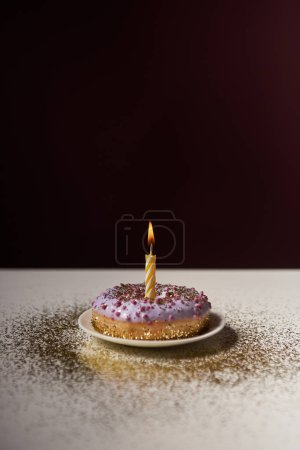 Photo for Burning candle in middle of glazed doughnut with golden sparkles on white table isolated on black - Royalty Free Image