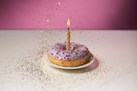 Photo for Burning candle in middle of doughnut with falling golden sparkles on white table on pink background - Royalty Free Image