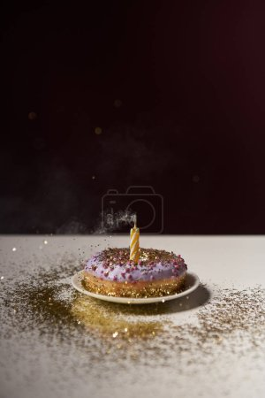 candle in middle of doughnut with golden sparkles on white table isolated on black