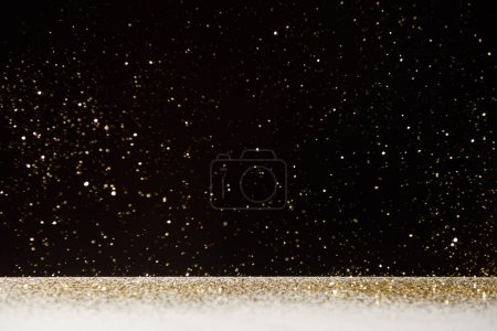 Photo for Selective focus of golden sparkles falling on white table isolated on black - Royalty Free Image
