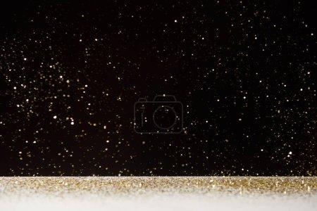 Photo pour Foyer sélectif d'étincelles dorées tombant sur une table blanche isolée sur du noir - image libre de droit