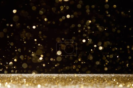 selective focus of bright sparkles falling on table isolated on black