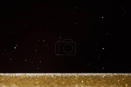 table avec des étincelles dorées brillantes isolées sur noir