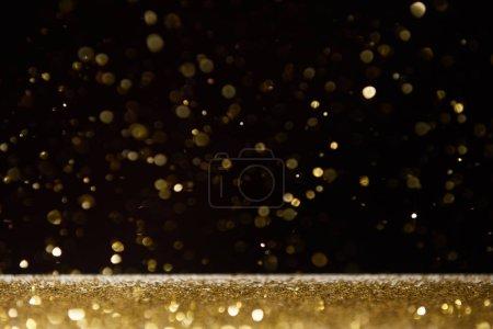 Foto de Foco selectivo de destellos brillantes dorados que caen sobre la mesa aislado en negro - Imagen libre de derechos