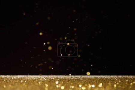Foto de Foco selectivo de brillantes destellos dorados en la mesa aislado en negro - Imagen libre de derechos
