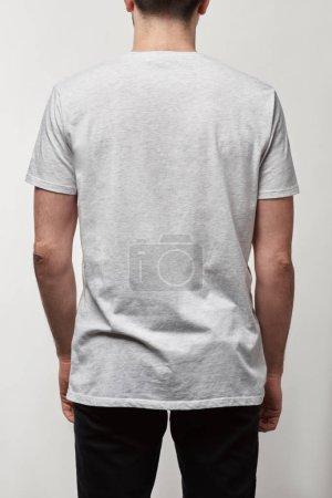 vue arrière de l'homme en t-shirt blanc décontracté avec espace de copie isolé sur gris