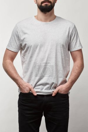 cropped view of bearded man with hands in pockets in white t-shirt with copy space isolated on grey