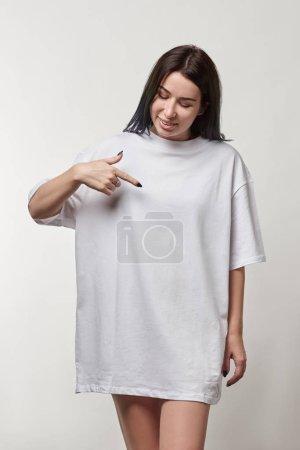 Photo pour Belle jeune femme pointant avec doigt blanc t-shirt oversize avec copie espace isolé sur fond gris - image libre de droit
