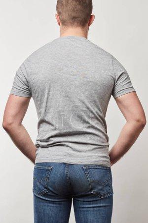 vista trasera del hombre en mezclilla y camiseta con espacio de copia aislado en gris