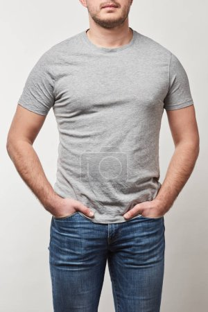 vista parcial del hombre con las manos en bolsillos en camiseta con espacio de copia aislado en gris