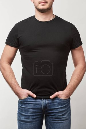 partial view of man with hands in pockets in black t-shirt with copy space isolated on grey