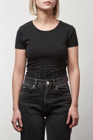 Teilbild einer jungen Frau in lässigem schwarzem T-Shirt mit Kopierraum auf weißem Hintergrund