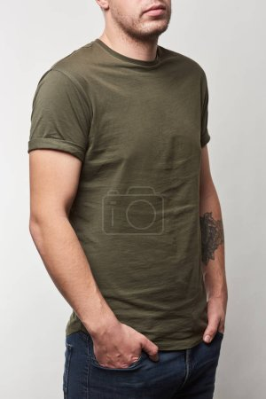 cropped view of tattooed man in khaki t-shirt with copy space isolated on grey