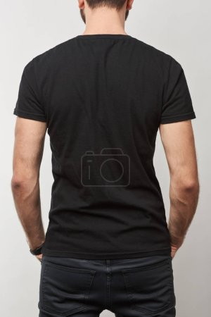back view of man in black cotton t-shirt with copy space isolated on grey
